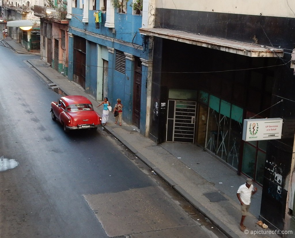 This girl extends a hand and the colectivo taxi pulls to the curb.  Nearly all of these colectivos in Havana are classic American cars.